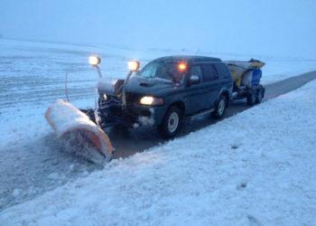 Jeep met sneeuwschuif en zoutstrooier